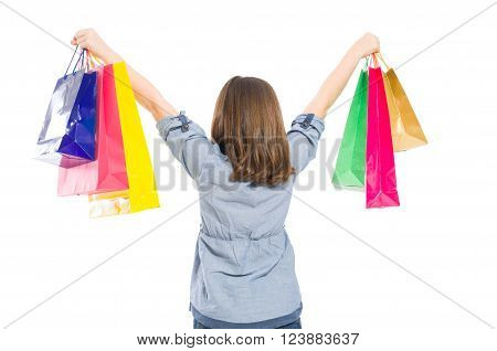 Young shopping girl from behind raising arms with bags