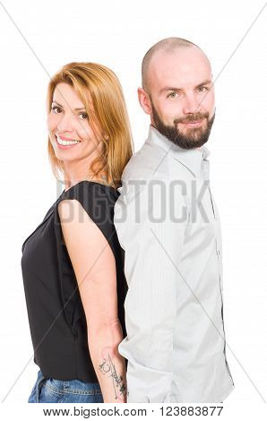 Beautiful young couple standing back to back and smiling on white studio background