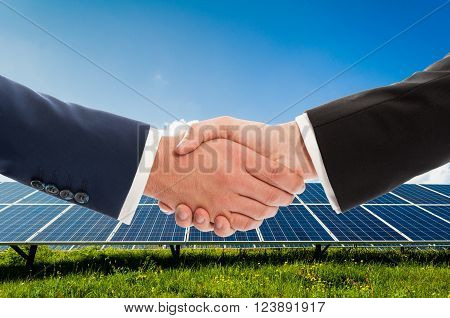 Businessmen handshake on solarpower photovoltaic panel background as bio-energy business team agreement