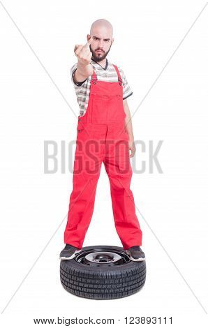 Mechanic Standing On Top Of Car Wheel Showing Middle Finger