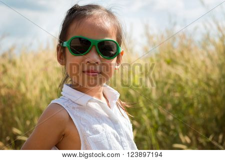 Happy little girl wearing sunglasses on grass background.
