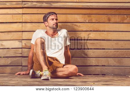 Handsome young man outside wearing white t-shirt and brown shorts posing and sitting down