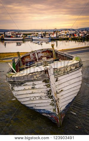 A fishing boat in need of attention sits in a boatyard near Poole Quay