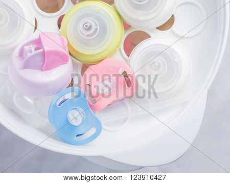 Steam sterilizer and dryer for sterilize baby accessories. Nipple teethers and milk bottles in steam sterilizer and dryer. Steam sterilizer used for sterilize baby accessories by high temperature steam. poster