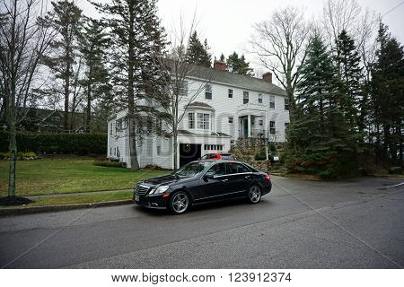 HARBOR SPRINGS, MICHIGAN / UNITED STATES - DECEMBER 23, 2015: A black Mercedes-Benz sedan sits parked beside a lakefront mansion on Glenn Drive in Harbor Springs.