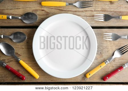 Plate and colorful flatware on wooden table, top view