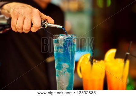 The bartender pours the liquor into an exotic cocktail.