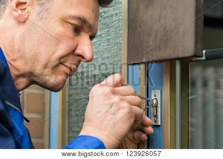 Mature Male Lockpicker Fixing Door Handle At Home poster