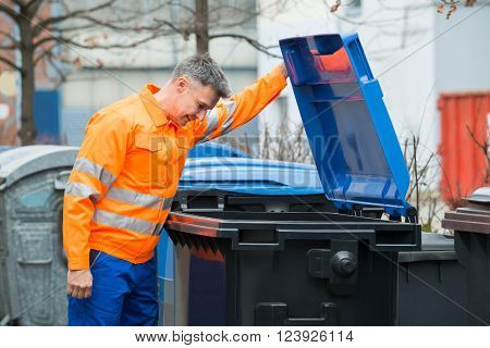 Working Man Looking In Dustbin On Street