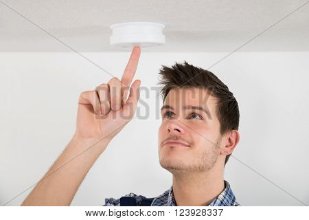 Male Electrician Testing Smoke Detector