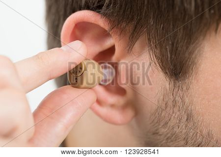 Close-up Of Young Man Wearing Hearing Aid In Ear