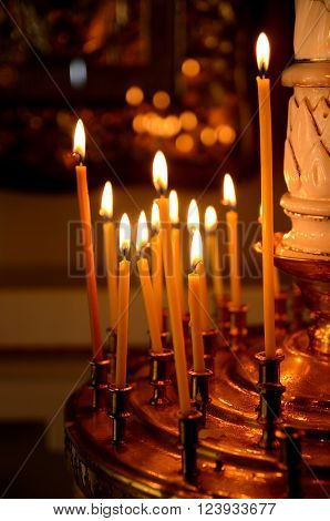 Wax candles burning in Orthodox church. Religious ritual.