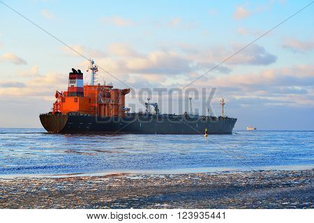 Cargo ship (bulk carrier) sailing in still frozen sea water along the coast