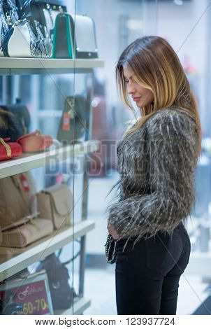 Attractive young woman fashion shot in mall. Beautiful fashionable young female in black jeans and fluffy jacket in shopping area. Long hair girl posing in front of show window with accessories