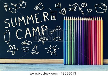 some drawings of summer stuff and the text summer camp written on a chalkboard and some colored pencils of different colors, on a blue rustic wooden table