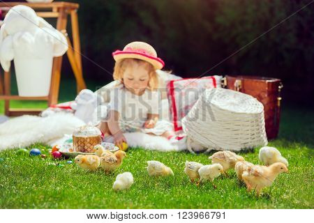 Cute little smiling baby girl in park on green grass. Poster for Easter holiday. Selective focus on chickens.