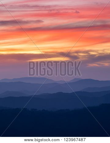 orange sunset sky with clouds mountain ranges in the foreground
