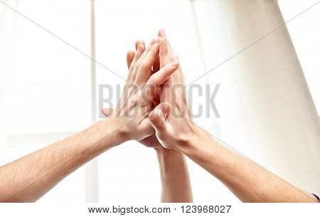 people, win, friendship, teamwork and success concept - close up of hands making high five gesture