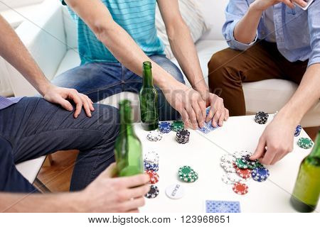 leisure, games, friendship, gambling and entertainment - close up of male friends playing cards and drinking beer at home