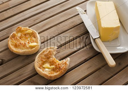 Buttered crumpets for breakfast with a pat of butter alongside on a plate served on a wooden table one crumpet bitten into
