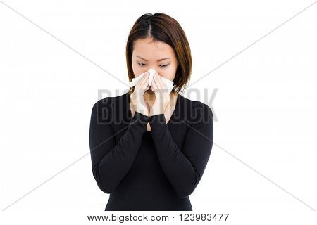 Sick woman blowing her nose with tissue paper on white background