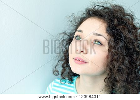Portrait of a beautiful young girl with curly hair on a gray background. Big green eyes and eyelashes closeup. Lookup