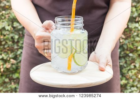 Hand on serving glass of iced lime soda drink stock photo