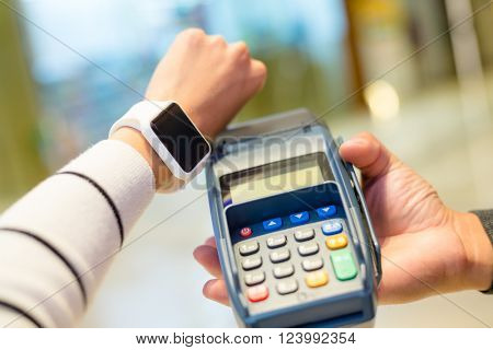 Woman using smartwatch for paying with NFC technology