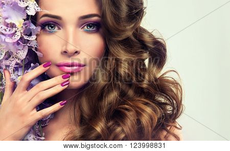 Beautiful girl with long wavy hair .  Brunette  model with curly hairstyle . Makeup and manicured nails