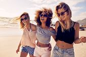 Group of beautiful young women strolling on a beach. Three friends walking on the beach and laughing on a summer day enjoying vacation. poster