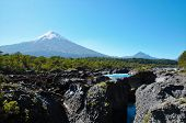 The waterfalls close to Puerto Varas: Saltos del Petrohue with the vulcano Osorno in the background poster