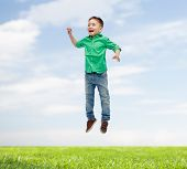 happiness, childhood, freedom, movement and people concept - happy little boy jumping in air over blue sky and grass background poster