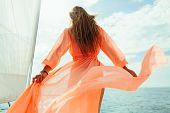 sexy woman in swimwear pareo yacht sea cruise luxury travel vacation with sunlight and blue sky. Back view poster