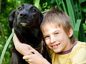 Young boy hugging  black dog outdoors poster
