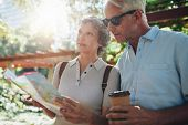 Close up portrait of senior couple using a map for directions. Retired couple exploring new places to visit during their vacation. poster