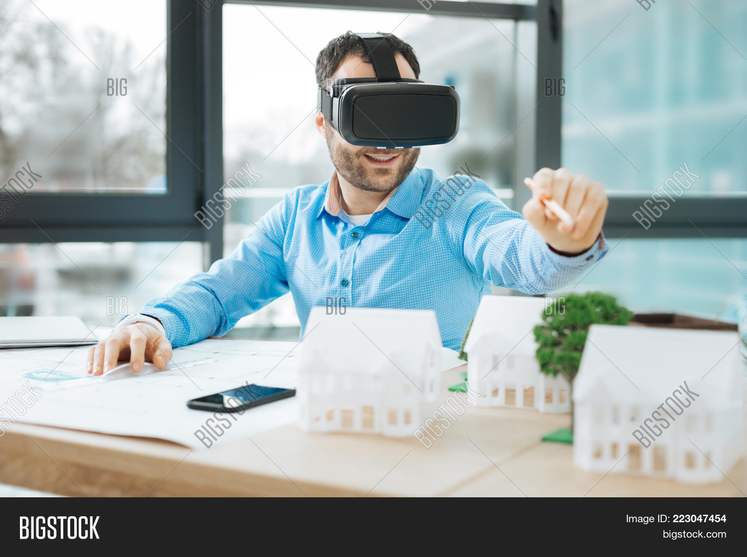 Augmented reality image photo free trial bigstock augmented reality cheerful young man wearing a vr headset and pointing at a virtual object malvernweather Gallery