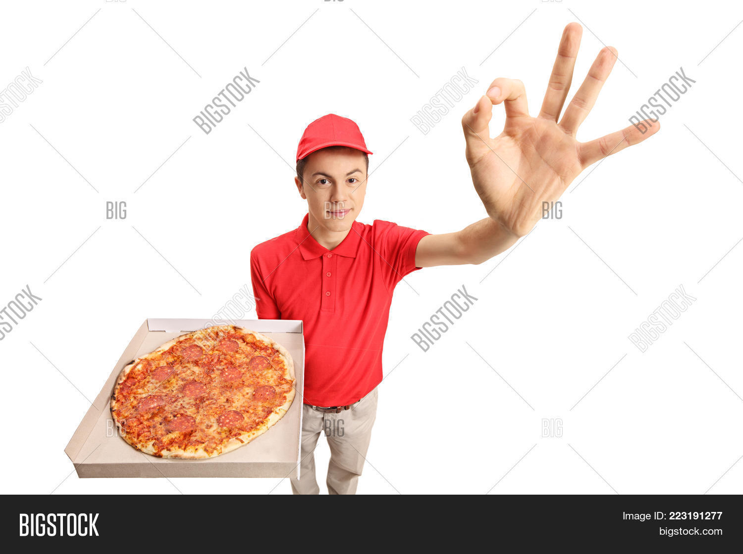 8e5a3aa206 Teen pizza delivery boy making an ok gesture isolated on white background
