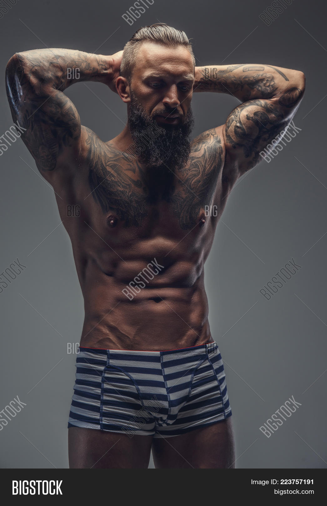 63e8b7366 Tattooed bearded man in stripes panties holding arms behaind his head.  Isolated on grey background