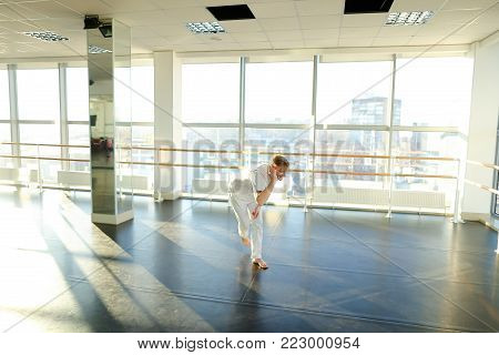 Novice dancer waiting trainer fooling, tattooed boy hopping waving hands. Fair-haired young man with mustache in spacious well-lit gym with big windows and mirrors. Concept of choreographic school, dancing courses or well-equipped hall
