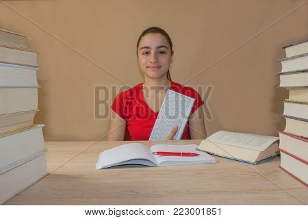 Smiling teenager girl doing homework at the table at home. Young Girl student with pile of books and notes studying indoors