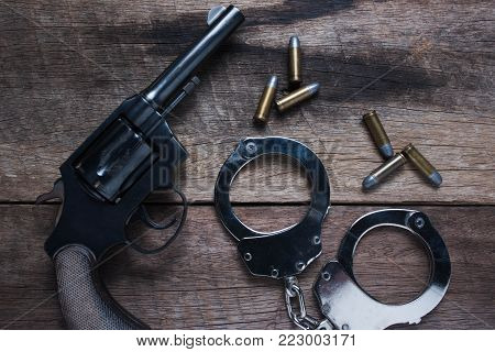Gun with ammunition and shackle on wood background, Top view