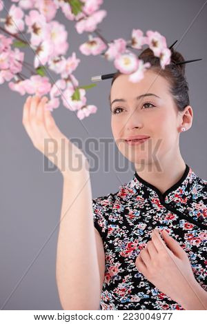 Beautiful young woman in asian outfit, reaching up for cherry flower, smiling.
