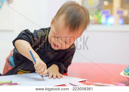 Cute little Asian 18 months / 1 year old toddler baby boy child drawing with pencil at art class, kid write with nursery teacher in a kindergarten,Creative play for toddlers concept