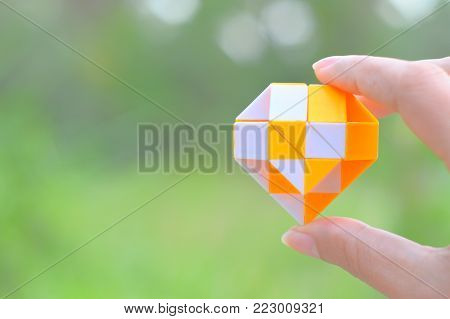 Little heart by yellow,white magic snake ruler twisty toy puzzle in an Asia man hand with blurred green nature background and copy space.Yellow heart is symbol of romantic love,Concept for valentine's