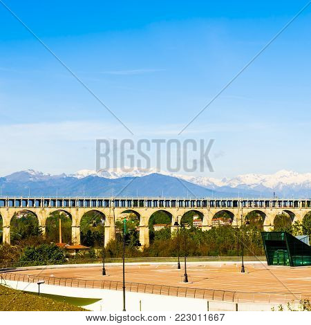 Automotive and railway aqueduct in Piedmont on the Background of Snow-capped Alps. Car parking in the foothills of the Italian mountains.