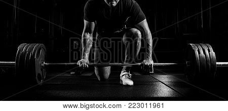 Professional Athlete Bent Over The Barbell And Is Preparing To Lift A Very Heavy Weight.