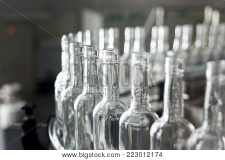 Empty glass bottles on the conveyor. Factory for bottling alcoholic beverages. Production and bottling of alcoholic beverages.