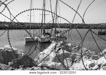 Breakwater protecting the beach of Mediterranean sea in Israel. View of the port of Tel Aviv for mooring yachts through the barbed wire. Black and white picture