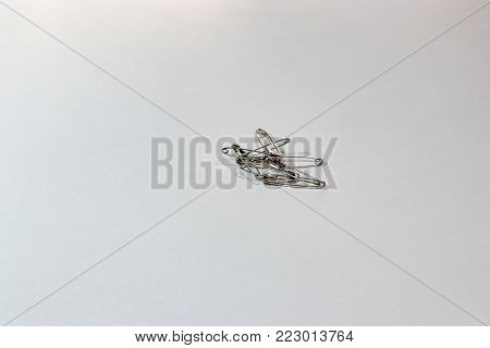 pile of tangled safety pins on a white background