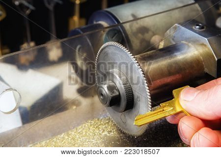 Golden key in a locksmith hand in a  workshop. Close up..